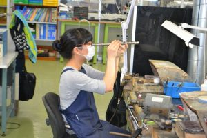 Miyazawa Flutes factory worker inspecting flute tube